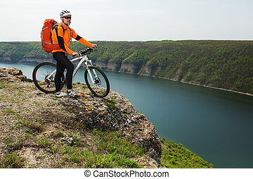 Cyclist in Orange Wear Riding the Bike Down Rocky Hill under...