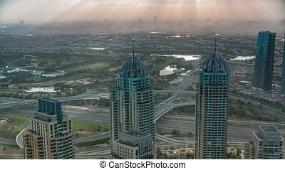Morning in Dubai Marina with towers and traffic on road from...