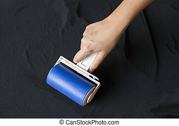 Lint roller on black cloth.