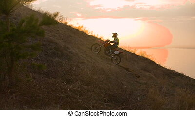 On the way to achieve the goal. motocross bike at sunset on hill climbs.
