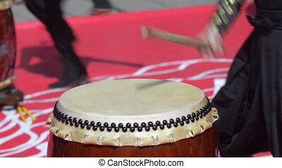 Japanese artist playing on traditional taiko drums -...