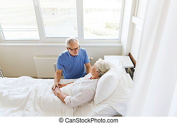 senior couple meeting at hospital ward - medicine, age,...