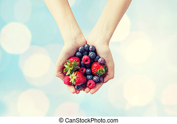 close up of woman hands holding berries - healthy eating,...
