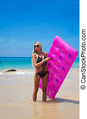 Slim blonde woman with pink swimming mattress on tropical beach