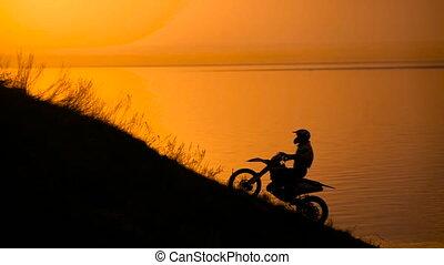 success. motocross bike at sunset on hill climbs.