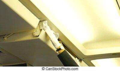 Steward or stewardess closing overhead cabin on airplane