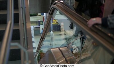 Dofferent people, men and women, going down on escalator in airport terminal