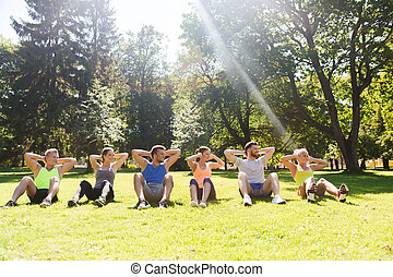 group of friends or sportsmen exercising outdoors - fitness,...