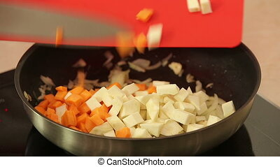 Chef stewing chopped vegetables in a pan