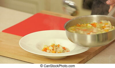 Serving soup with beans and vegetables - Chef is serving...