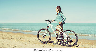 Girl with bicycle on beach - Beautiful girl walking with...