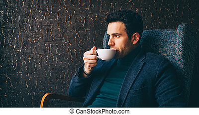 Young man drinking a coffee at the cafe