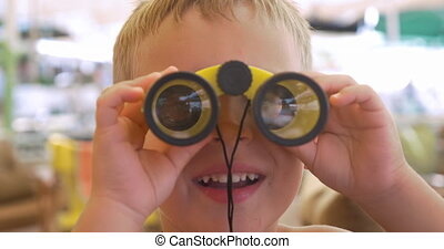 Child looking through the binoculars - Close-up shot of a...