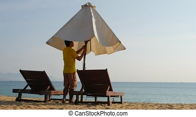 Young man standing bitween beach loungers and opening an...