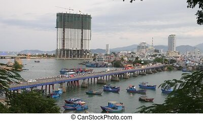 Traffic in a bridge. City bay with blue boats and buildings...