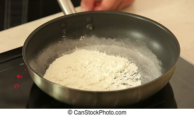 Preparation of bechamel sauce - White flour on a pan during...