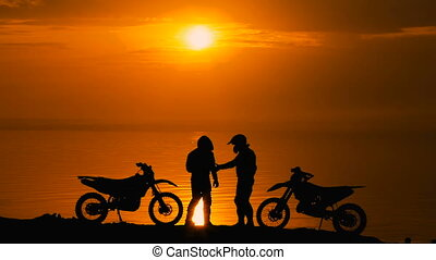 Two other motorcyclists met at beoregu river at sunset. They are happy to see each other and greet. Silhouette against the background of water and sky,