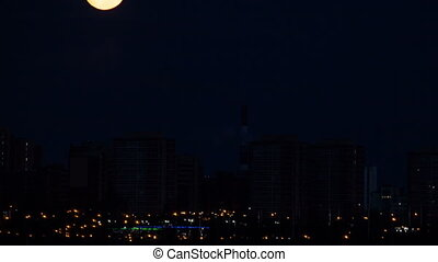 Moonset Over City Timelapse Night moon setting over a small...