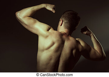 Muscular man shows his biceps back. Athletic man on a dark...