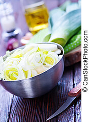 fresh leek in metal bowl and on a table