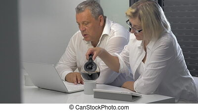 Mature Businesspeople with Coffee and Laptop - Two mature...