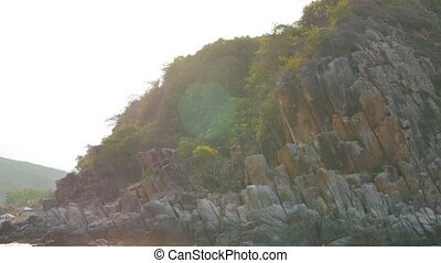 Rocky shore with trees in rays of sun. Panoramic view from moving boat