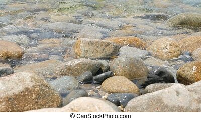 Stones on the sea shore and waves of clear sea water
