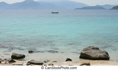 Lonely empty boat anchored in a sea bay and floating on calm turquoise water