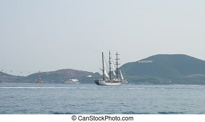 Three mast yacht drifting in the Nha Trang bay, Vietnam. Vinpearl on the background. View from a moving boat.