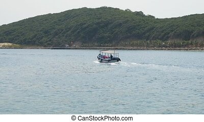 Small blue motorboat with single person aboard in see bay in Vietnam. Woody mountain in the background.