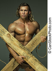 Men with perfect muscular torso, holding hands wooden beams...