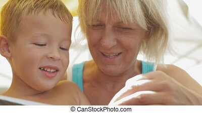 Grandmother reading a book to grandson - Close-up shot of a...
