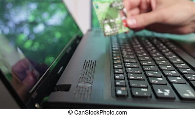 man using computer for on line purchase with credit card. -...