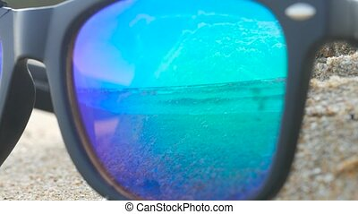 Blue mirrored sunglasses lying on sand and reflecting sea...