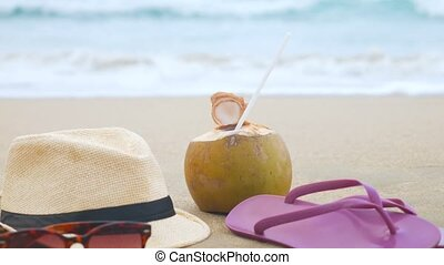 Coconut with drinking straw, hat, sunglasses and beach...