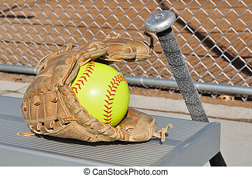 Yellow Softball, Bat, and Glove on an Aluminum Bench
