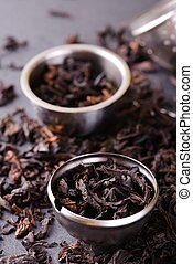 Strainer and metal bowl full of dry tea leaves - Vertical...