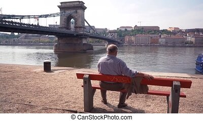 An Old man sitting alone on bench and looking at the river