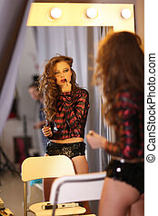 Stylish woman applying lipstick at front of mirror in studio...