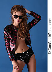 Gorgeous erotic brunette woman in sequins shorts, jacket and...