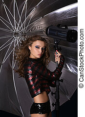 Beautiful woman with tripod on background of silver umbrella...