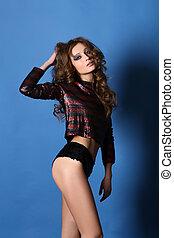 Studio portrait of brunette in a sequins jacket and shorts -...