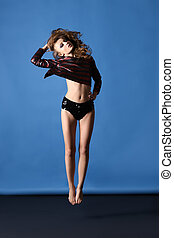 Attractive sexy model with perfect body is jumping in studio...