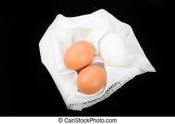 Boiled eggs isolated on black background - three chicken...