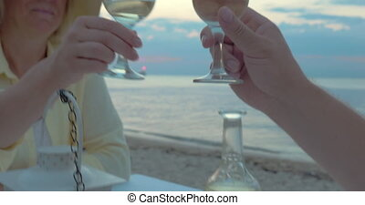 Couple toasting with wine in beach restaurant - Steadicam...