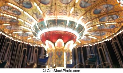 Out of focuse whirling empty carousel with blinking lights