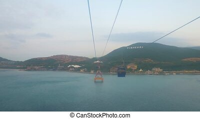 Travelling to Vinpearl by cable car. Anothe cabi passes by the camera. Nha Trang, Vietnam.