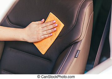 Hand with microfiber cloth cleaning car