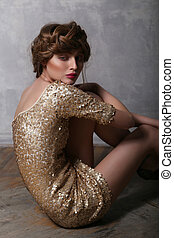 Fashion girl in gold dress sitting on the floor at studio