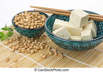 Tofu cut into cubes with soybeans in bowl, on white...